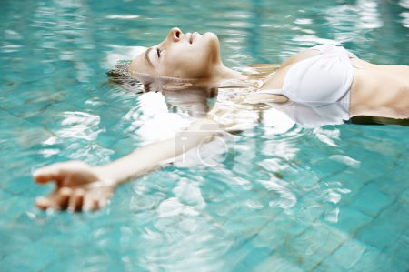 Attractive young woman floating in a swimming pool with her arms outstretched.