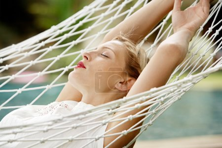 Young attractive woman with red lipstick laying down on a white hammock