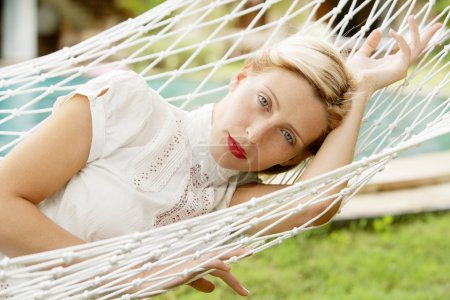 attractive woman laying and relaxing on a white hammock