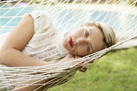 Photo pour Gros plan portrait d'une jolie femme blonde allongée sur un hamac dans un jardin, regardant la caméra . - image libre de droit