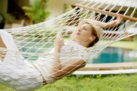Attractive young woman laying down and relaxing on a white hammock
