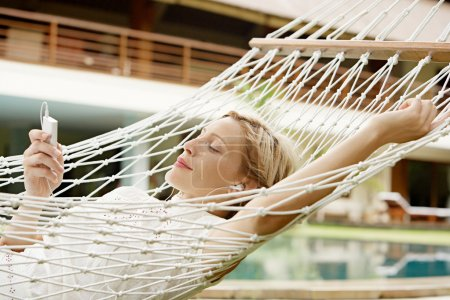 Attractive woman using an mp4 player to listen to music with headphones while laying in a hammock