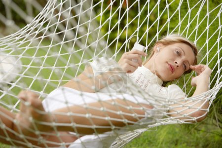 Young beautiful woman laying down on a hammock while on vacations