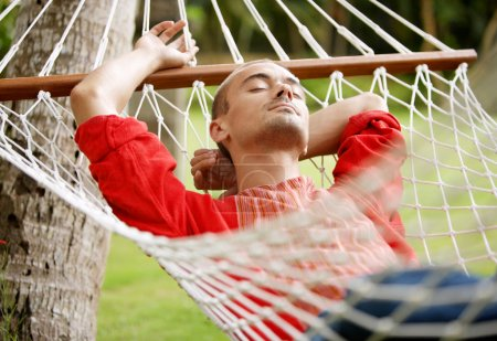 Photo for Attractive young man laying down on a hammock in a tropical home's garden, relaxing. - Royalty Free Image