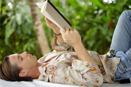 attractive young man reading a book