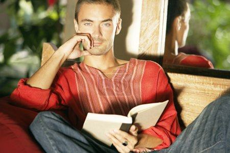 Young man reading a book while seating in a garden sofa outdoors.