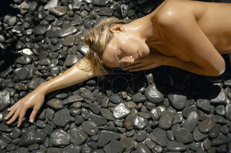 Young woman laying down nude on a bed of black stones outdoors.