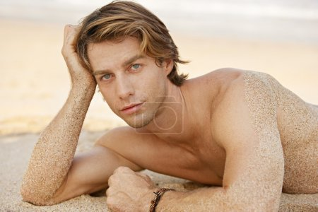 Portrait of an attractive young man sunbathing on the beach.