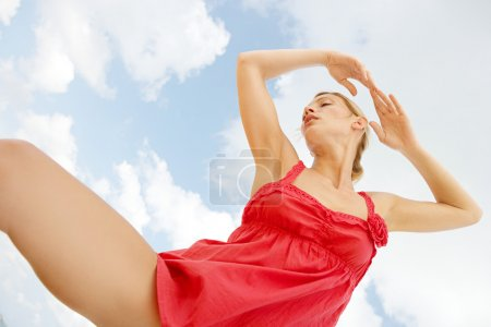 Photo for Under view of an attractive woman dancing against a blue sky. - Royalty Free Image