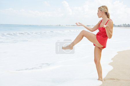 Attractive young woman balancing herself on one leg while practicing martial arts on the beach.