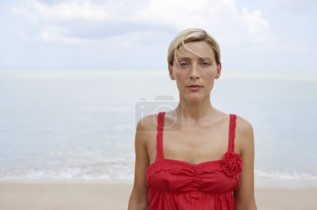 Portrait of an attractive blonde woman standing by the sea.