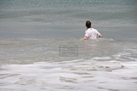 Photo pour Jeune homme dans l'océan, faisant face à de grandes vagues venant son chemin . - image libre de droit