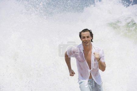 Photo pour Attrayant yound homme héroïquement courir hors de la mer, entouré de vagues dramatiques s'écrasant . - image libre de droit