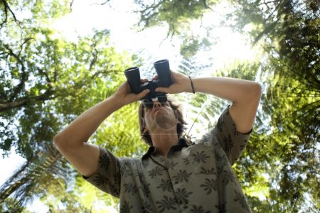 Photo for Underview of a man looking through binoculars in the forest. - Royalty Free Image