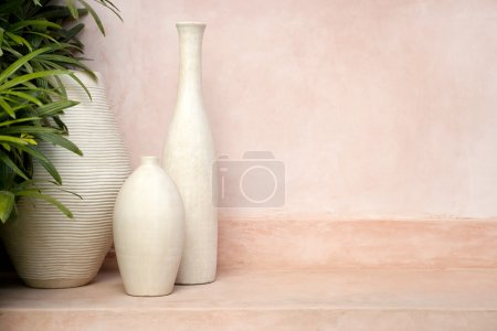 Vases standing on a step with a pink background.
