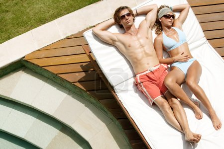 attractive couple sunbathing by a swimming pool while on holiday.