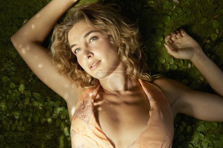 young woman laying down on a bed of small heart shaped leaves.