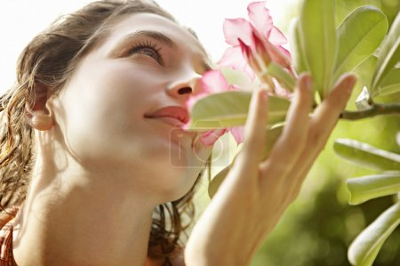 beautiful young woman holding a flower close to her nose