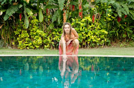 woman crouching by swimming pool and touching the water.