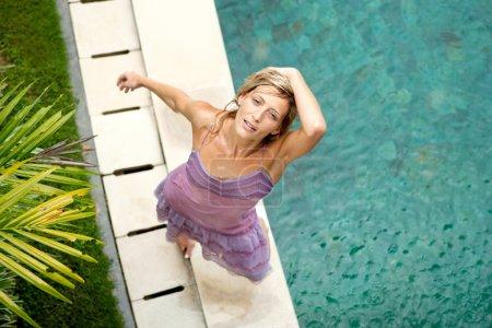 Photo pour Au-dessus de la tête d'une femme près d'une piscine sous la pluie en été, souriant . - image libre de droit