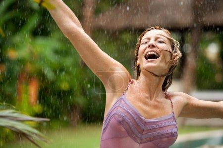 Photo pour Portrait d'une belle femme heureuse profitant de la pluie tropicale tombant sur elle dans un jardin exotique . - image libre de droit