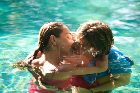 exy young couple submerged in a swimming pool while dressed