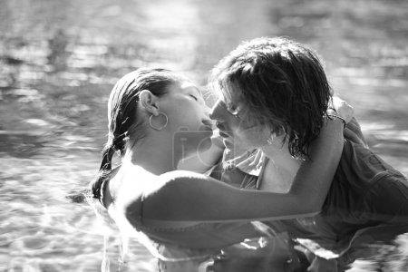 sexy young couple submerged in a swimming pool while dressed