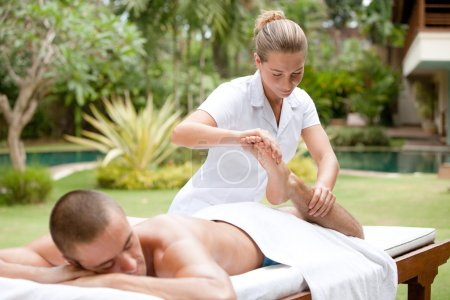 Young masseuse massaging and stretching the body of an attractive man in a tropical hotel garden