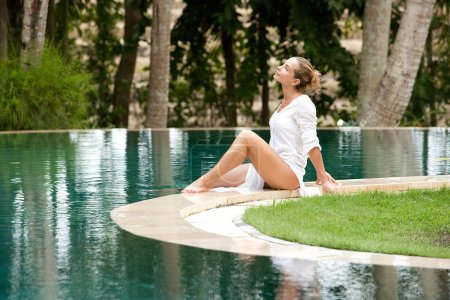Attractive young woman sitting down at the edge of a swimming pool