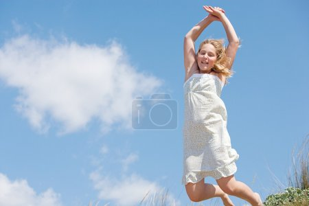 Young girl jumping on the beach dunes with a blue sky in the background.