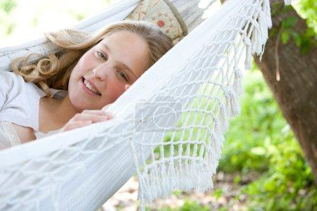 Photo pour Gros plan portrait d'une jeune adolescente allongée sur un hamac dans un jardin, souriant . - image libre de droit