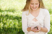Girl holding a baby bird in her hands while sitting down on a long green grass garden