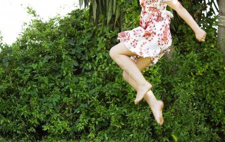Photo pour Partie du corps d'une jeune fille sautant dans les airs dans un jardin verdoyant . - image libre de droit