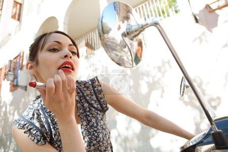 Photo pour Attrayant jeune femme en utilisant les miroirs sur sa moto pour appliquer rouge à lèvres sur elle-même par une journée ensoleillée, en plein air . - image libre de droit