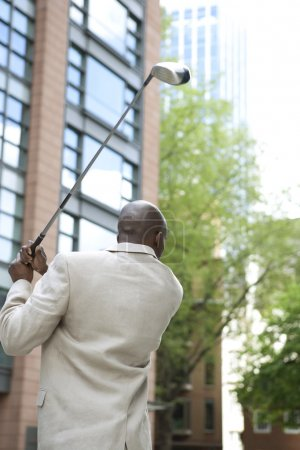 Photo for Businessman playing golf in the middle of the financial district. - Royalty Free Image