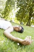 Indická dívka, kterým se stanoví za slunného dne na zelené trávě v parku