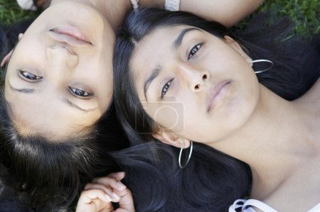 two indian girls laying down on grass with their heads together.