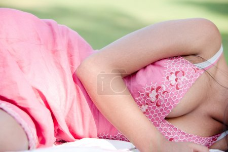 Body section of a teenage girl laying down on green grass in the park