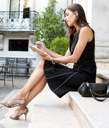 Photo pour Élégante femme d'affaires assise sur des marches de bâtiments classiques, prenant des notes dans son agenda . - image libre de droit