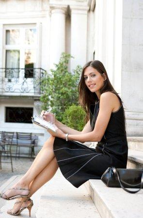 Photo pour Femme d'affaires élégante assise sur un bâtiment classique prend des notes dans son agenda, souriant . - image libre de droit