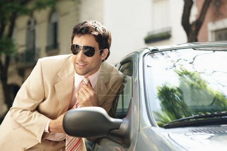 Attractive businessman tightening his tie while looking at himself in a car's reversing mirror