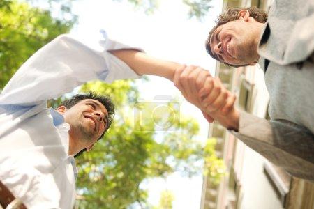 Photo pour En vertu de la perspective d'affichage de deux jeunes hommes d'affaires attrayants se serrant la main avec un ciel bleu avec des arbres dans la ville. - image libre de droit
