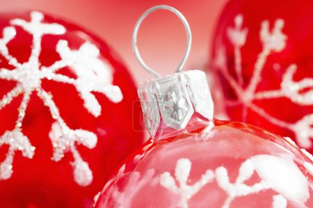 red and pink Christmas balls ornaments with a traditional snow flake drawn on them.