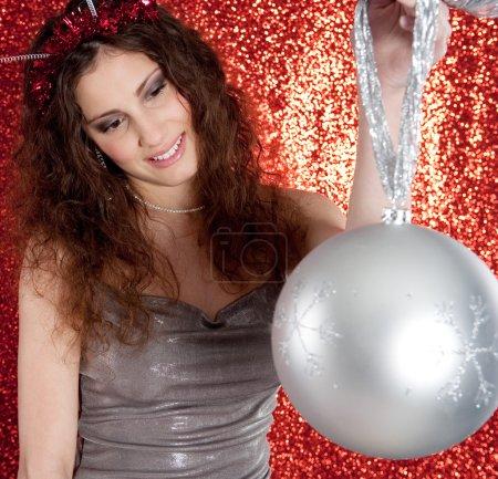 Foto de Vista de cerca de una atractiva mujer joven sosteniendo una gran bola de barball de árbol de Navidad en el aire mientras está de pie frente a un fondo de brillo rojo sonriendo . - Imagen libre de derechos