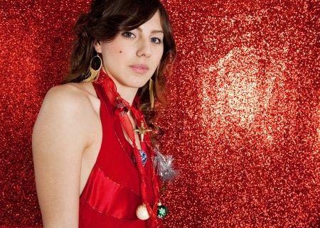 Foto de Hermosa mujer joven con decoraciones de árboles de Navidad como un collar mientras está de pie sobre un fondo de brillo rojo . - Imagen libre de derechos