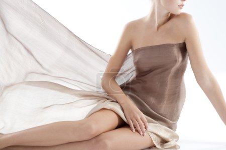 Close up of a woman's body wearing a transparent sarong.