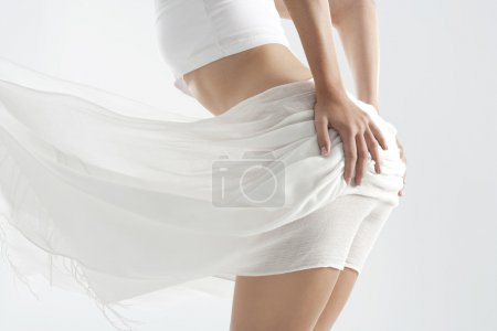 Mid section of a woman's body with floaty white fabric covering her.