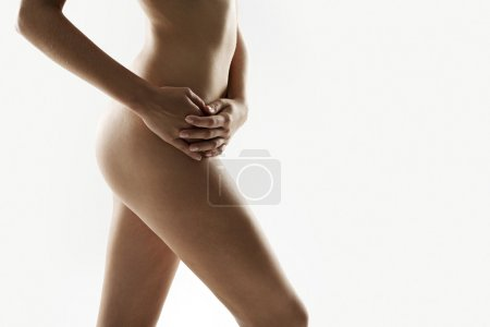 Mid section of a woman's naked body in silhouette