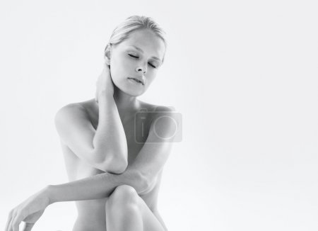 Black and white image of a naked woman holding her neck in pain