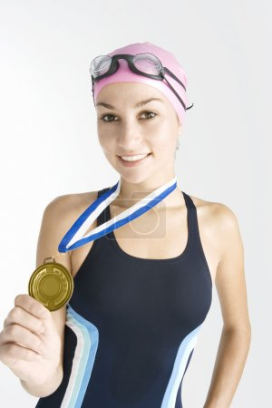 Young swimmer holding a gold medal while wearing a swimming costume
